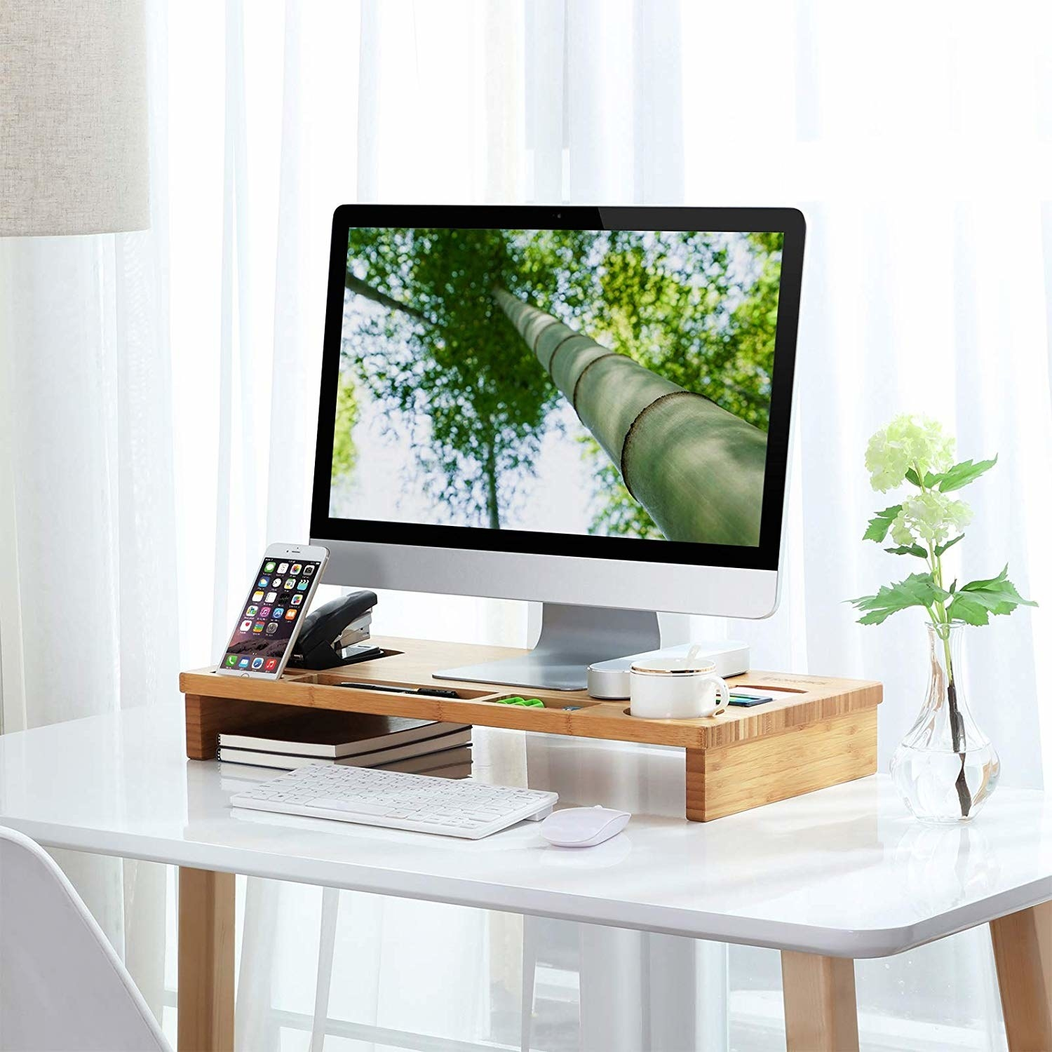 A large computer monitor on a sturdy bamboo stand