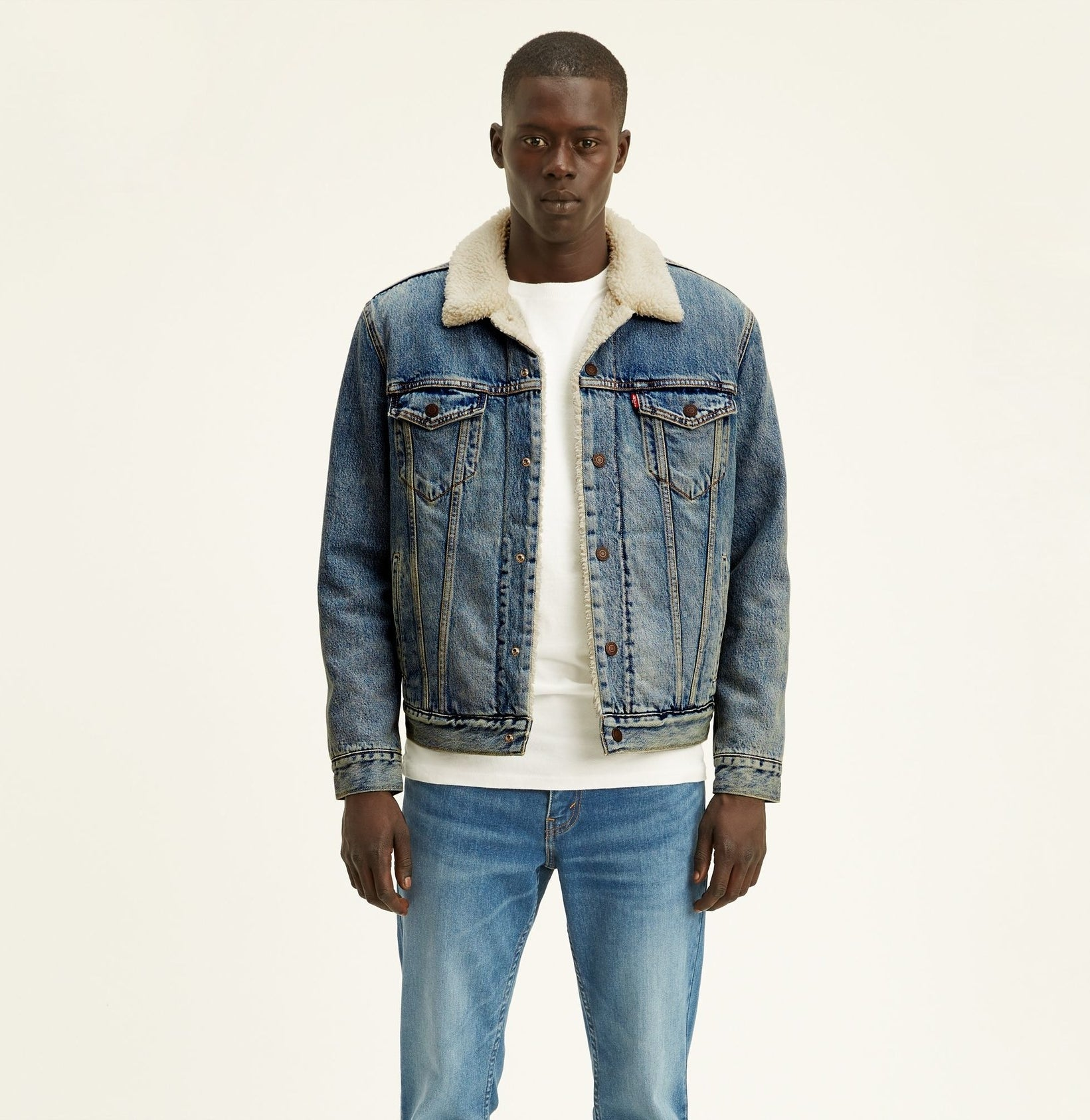 Model wearing the light wash denim jacket with a sherpa collar and lining