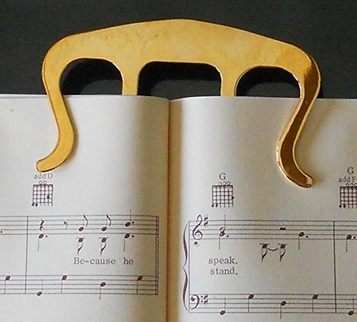 the golden clip holding the music book open from the top of it