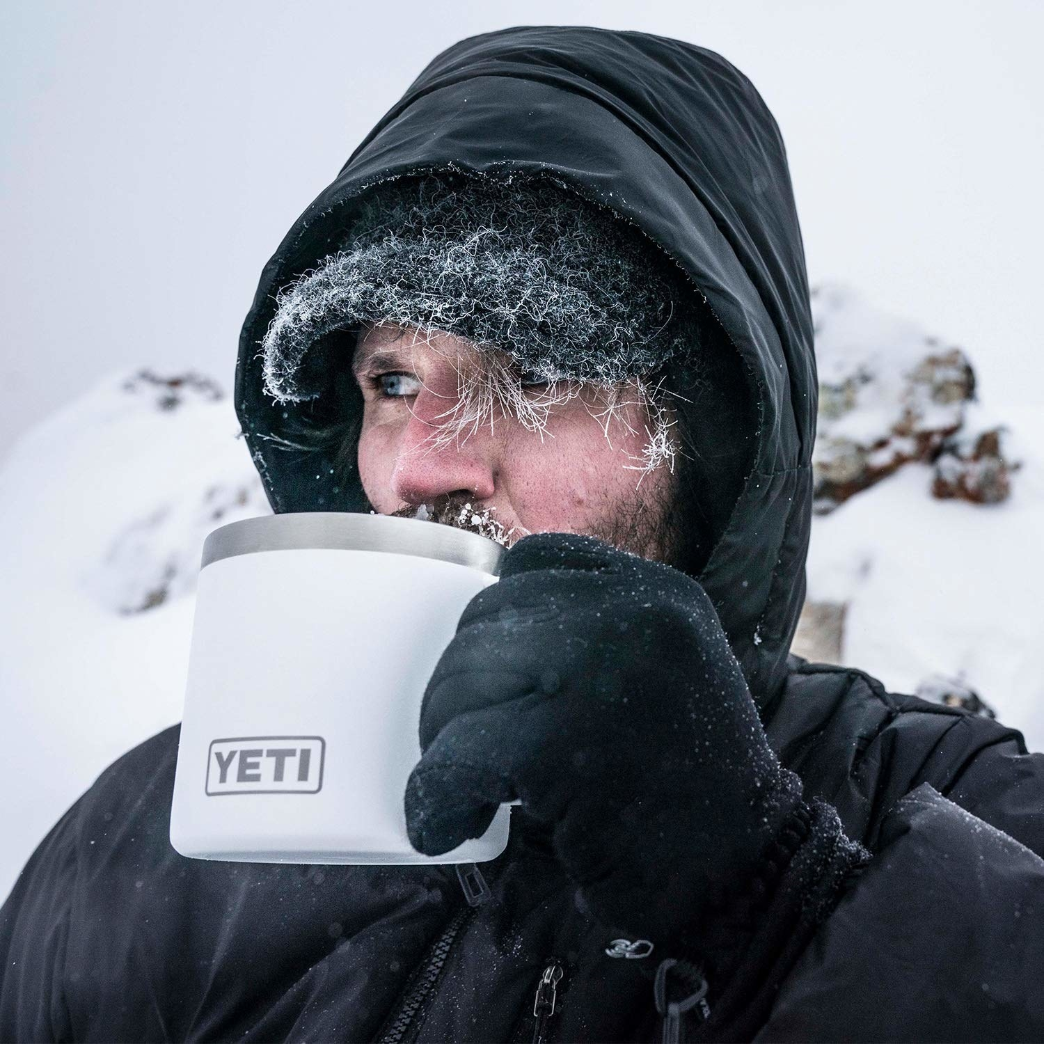 model in the snowy outdoors drinking from a white mug