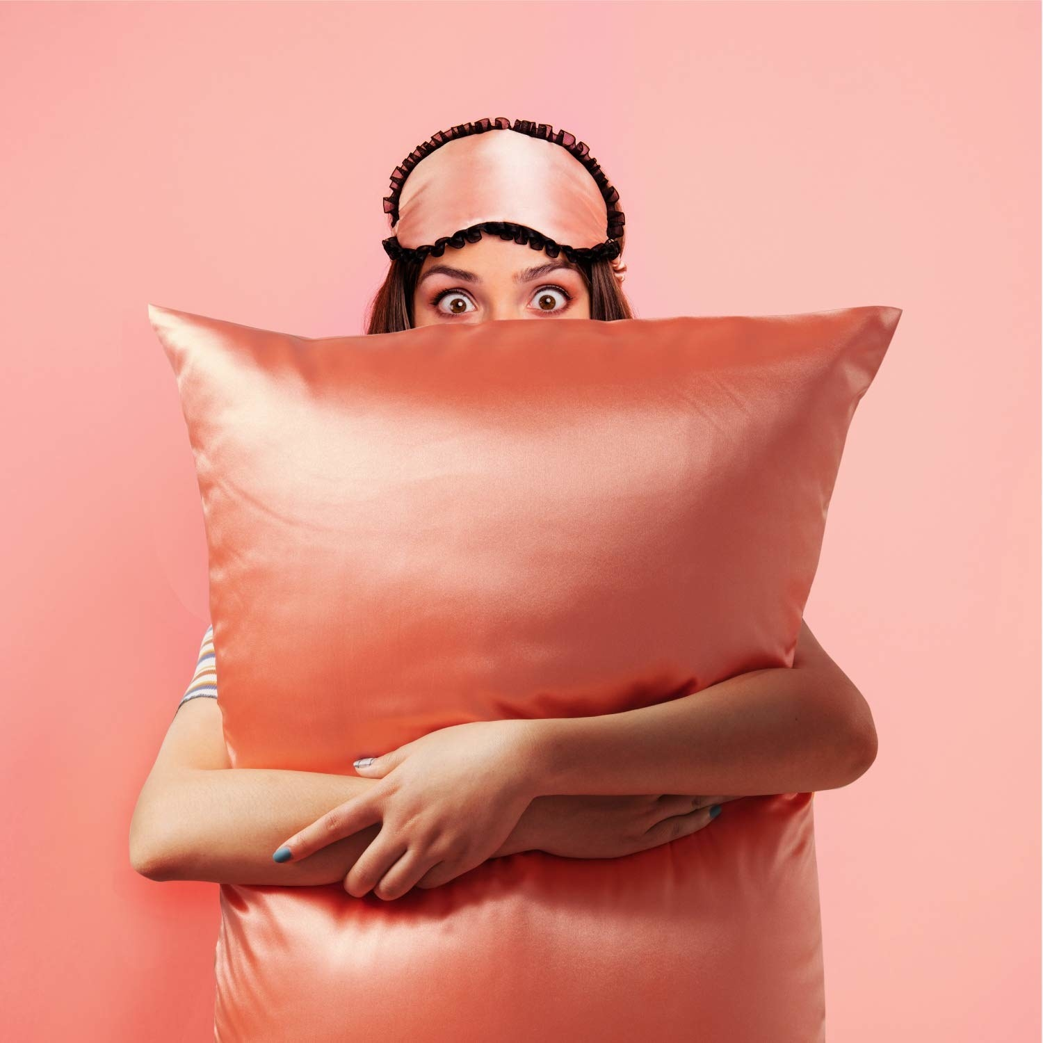 model holding pillow with light pink satin pillowcase