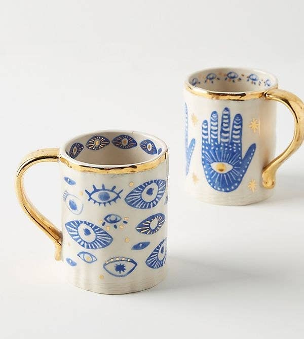 white mugs with blue eye designs and gold handles