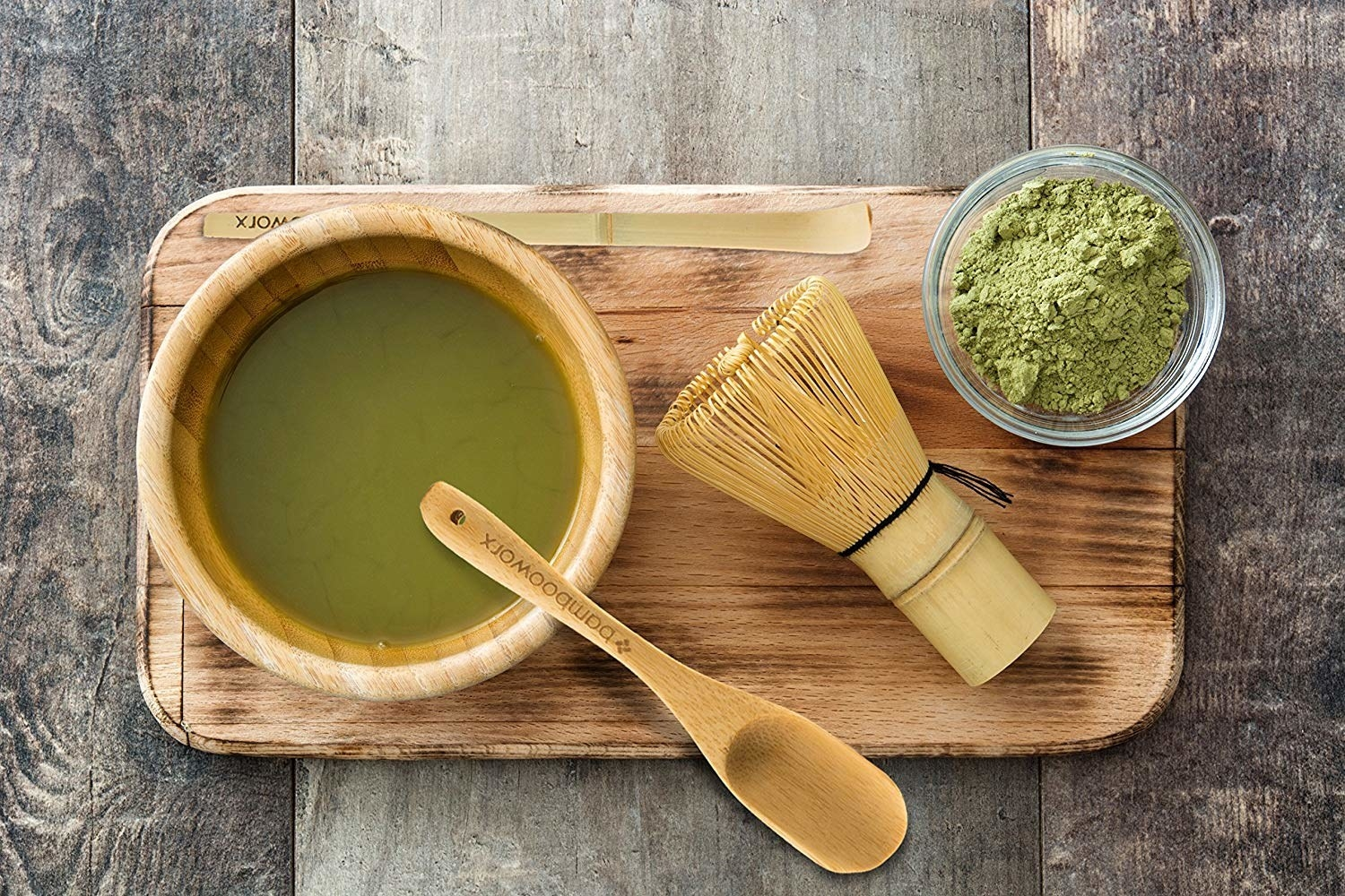 A wood bowl of matcha with a wood spoon, wood whisk, and small bowl of matcha powder on a wood board