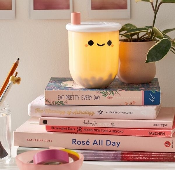 Small cup-shaped nightlight with a white lid, pink straw, black boba tea balls inside and a little face on the front