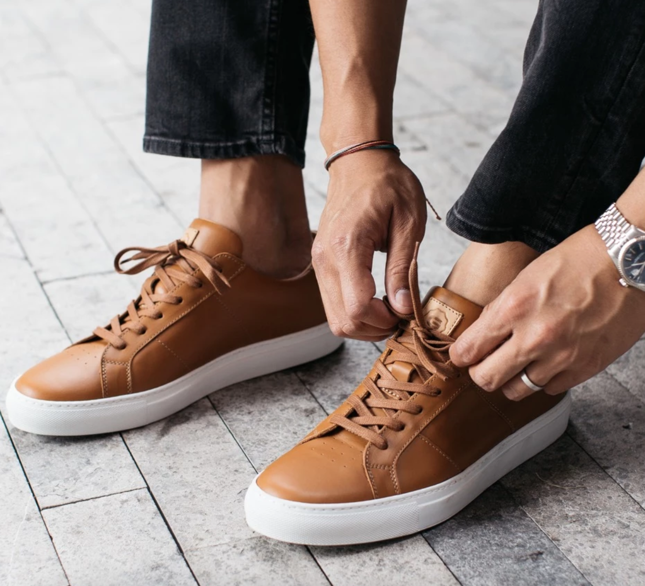 Model tying a pair of tan leather Greats
