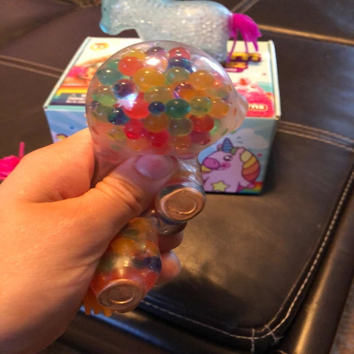 reviewer squeezes unicorn to show rainbow beads inside