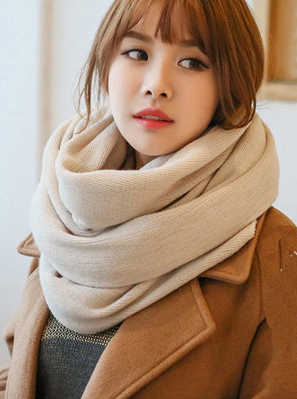 Model with a large beige scarf wrapped around their neck
