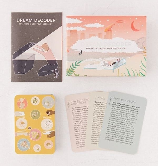 A dream decoder book and box with cards below it with illustrations and information on what dreams might mean