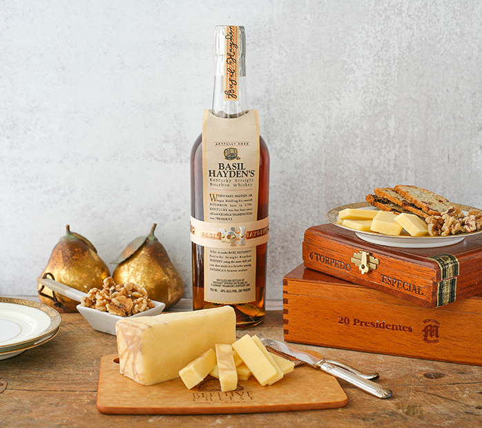 A block of cheese next to a bottle Basil Hayden's