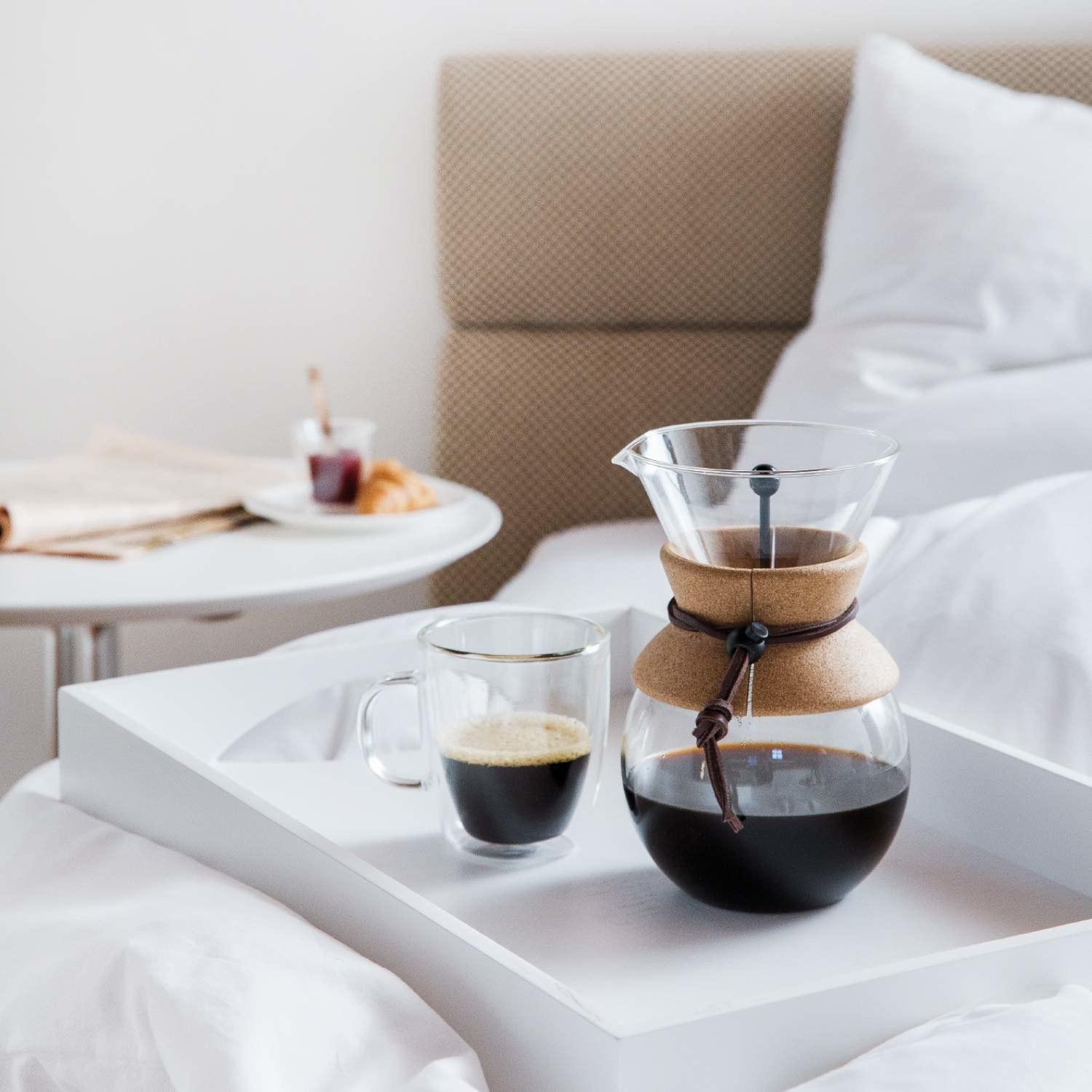 The coffee maker with cork in the middle with coffee in it and a coffee cup next to it
