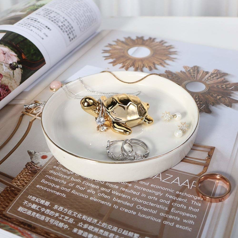 A white ceramic dish with gold trim and a small gold turtle in the center with assorted rings and jewelry on it