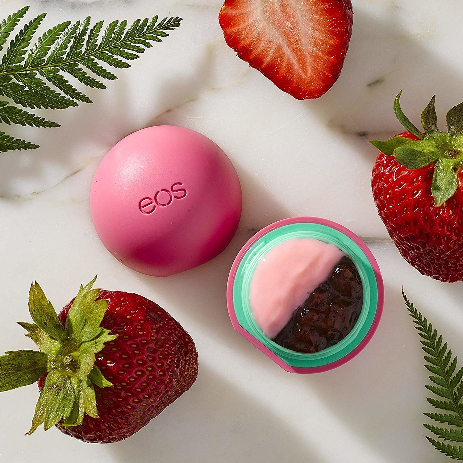 A small round container of lip balm with fresh strawberries around it