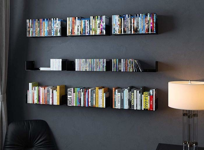 nine floating shelves ordered by threes so they look like three long shelves on a wall holding up books, CDs, and DVDs