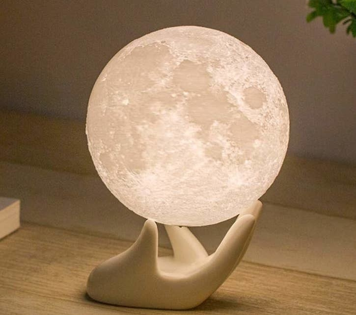 A circular moon-shaped light with a white ceramic hand holding it