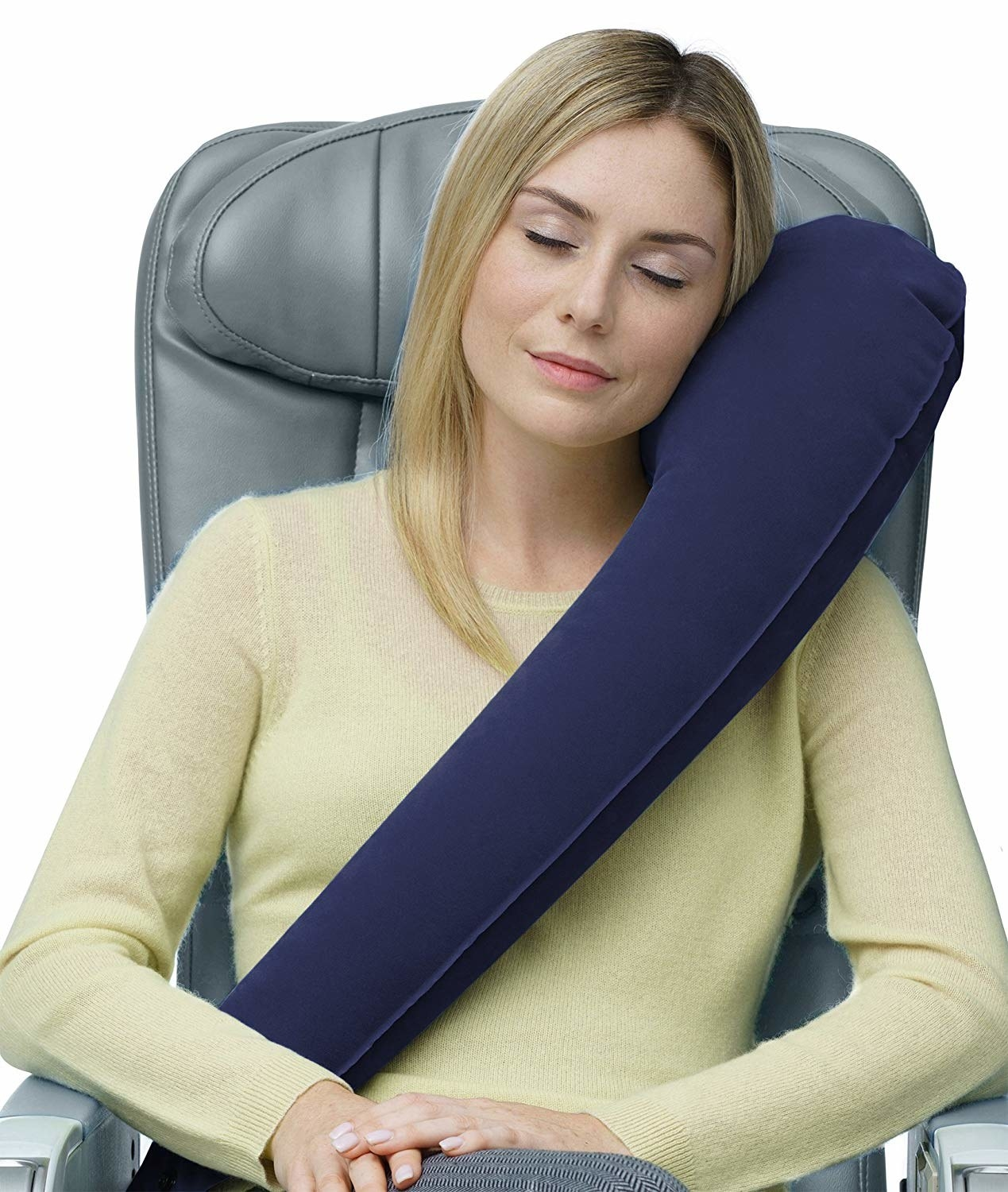 model with the inflated side sleeping pillow across one shoulder and in front of their body while sitting in a chair