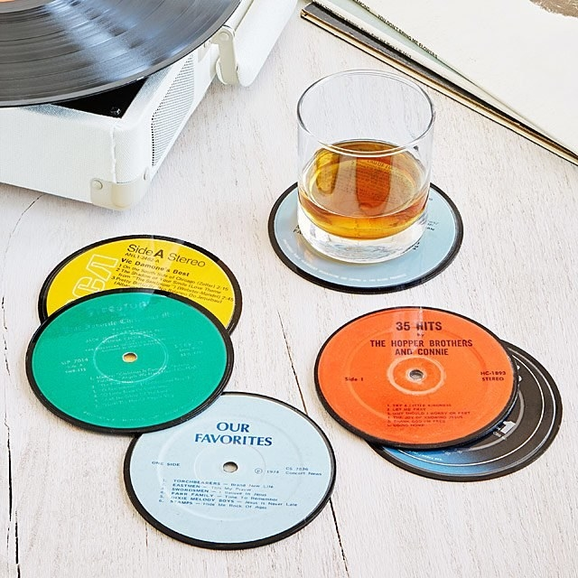 Six circular coasters that look like records with a glass on one of them