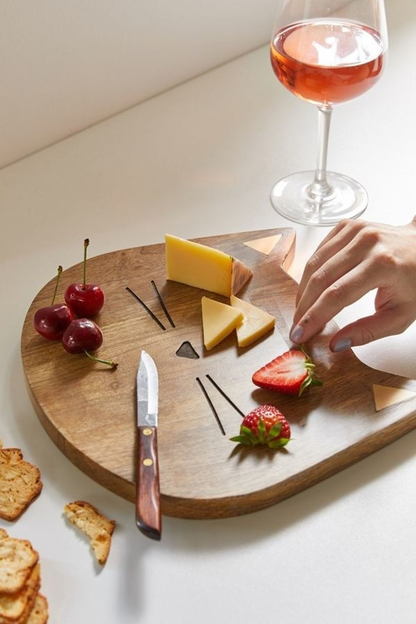 A cat-shaped wood cheese board with a small nose and whiskers on it