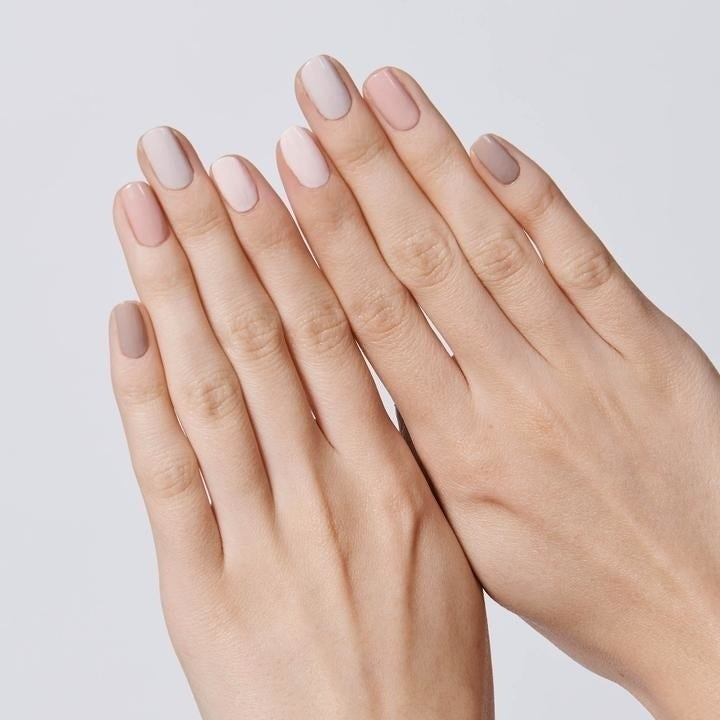 a model showing their nails with different neutral colors on each finger