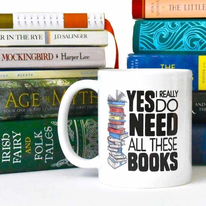 """a white mug that says """"Yes I really do need all these books"""" with a stack of books on it"""