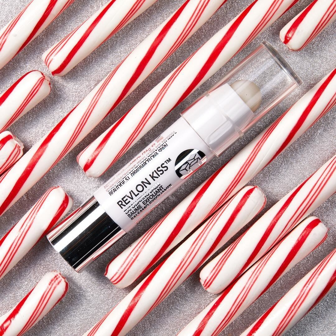 A tube of exfoliating lip balm surrounded by candy canes