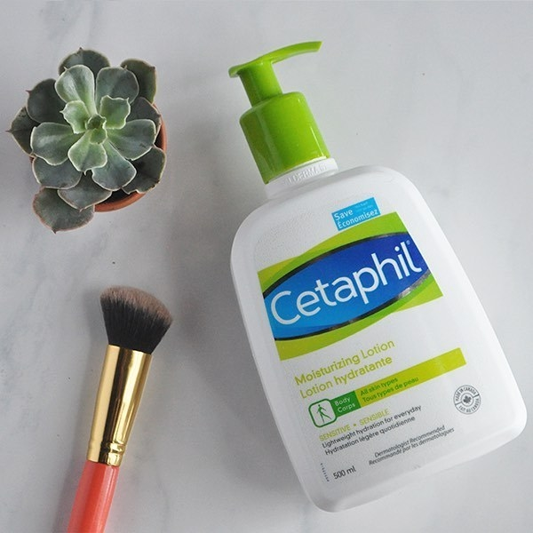 A small bottle of lotion lying flat on a plain background with a makeup brush and a plant nearby