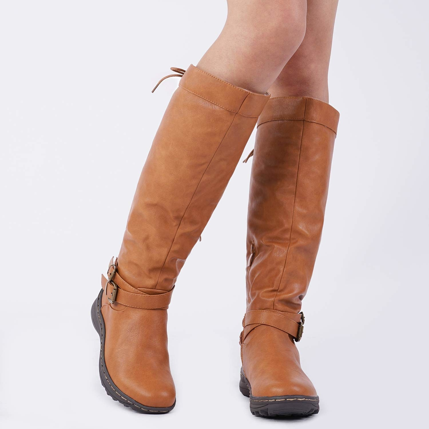 the knee-high boots in brown with two buckles around the ankles and black soles