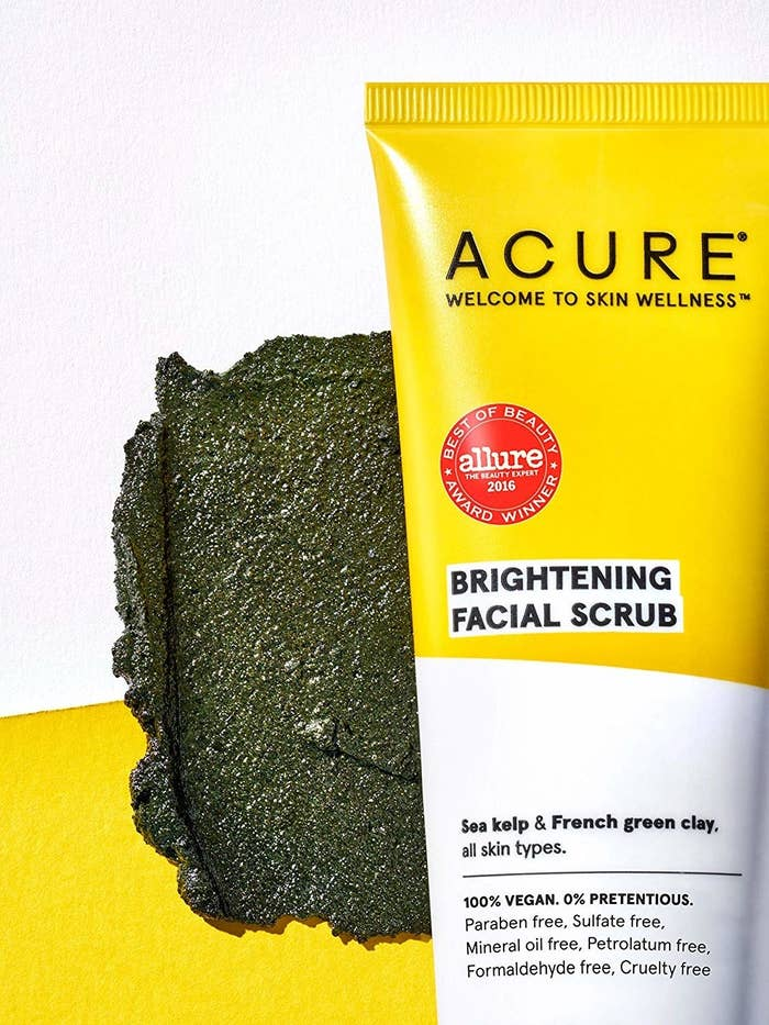 A patch of face scrub on a striped background with the bottle sitting next to it