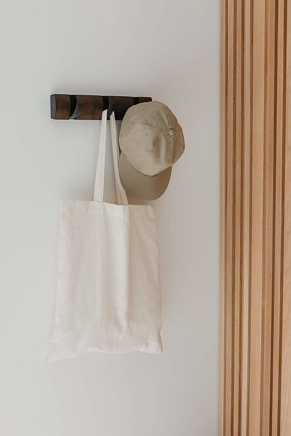 Hat and tote bag hanging on flip-up hook unit