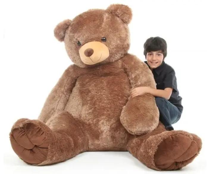 A kid hugging a giant teddy bear