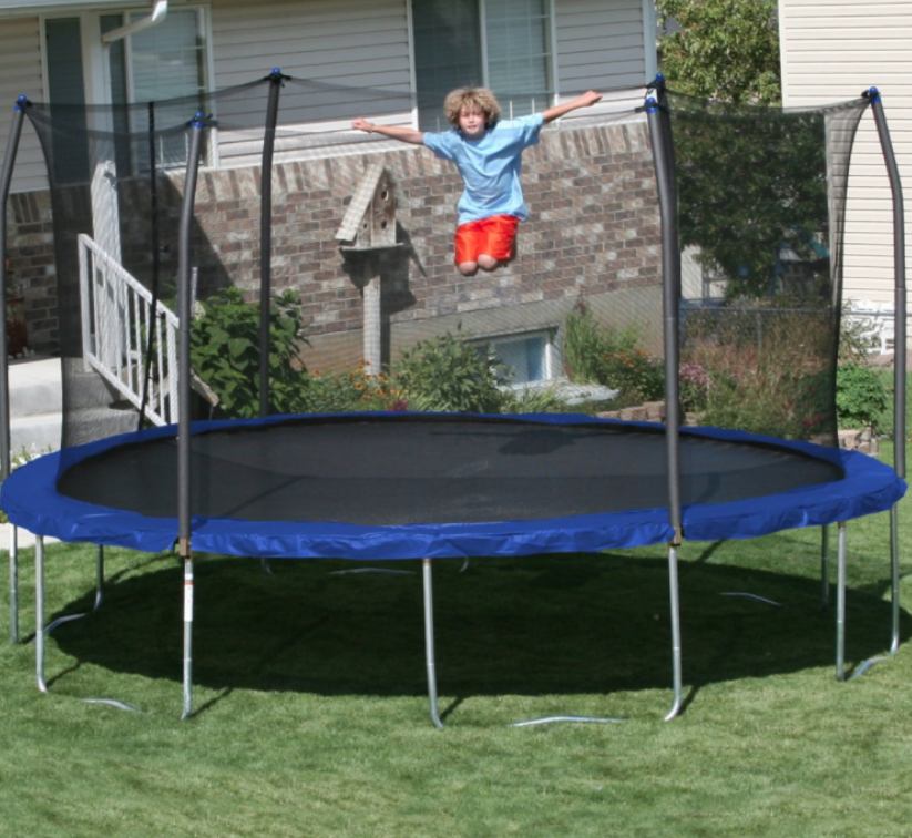 A kid jumping on a trampoline in the backyard