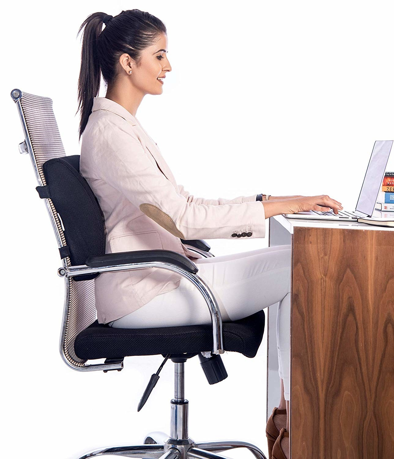 A woman working at her desk with the cushion attached to the chair.