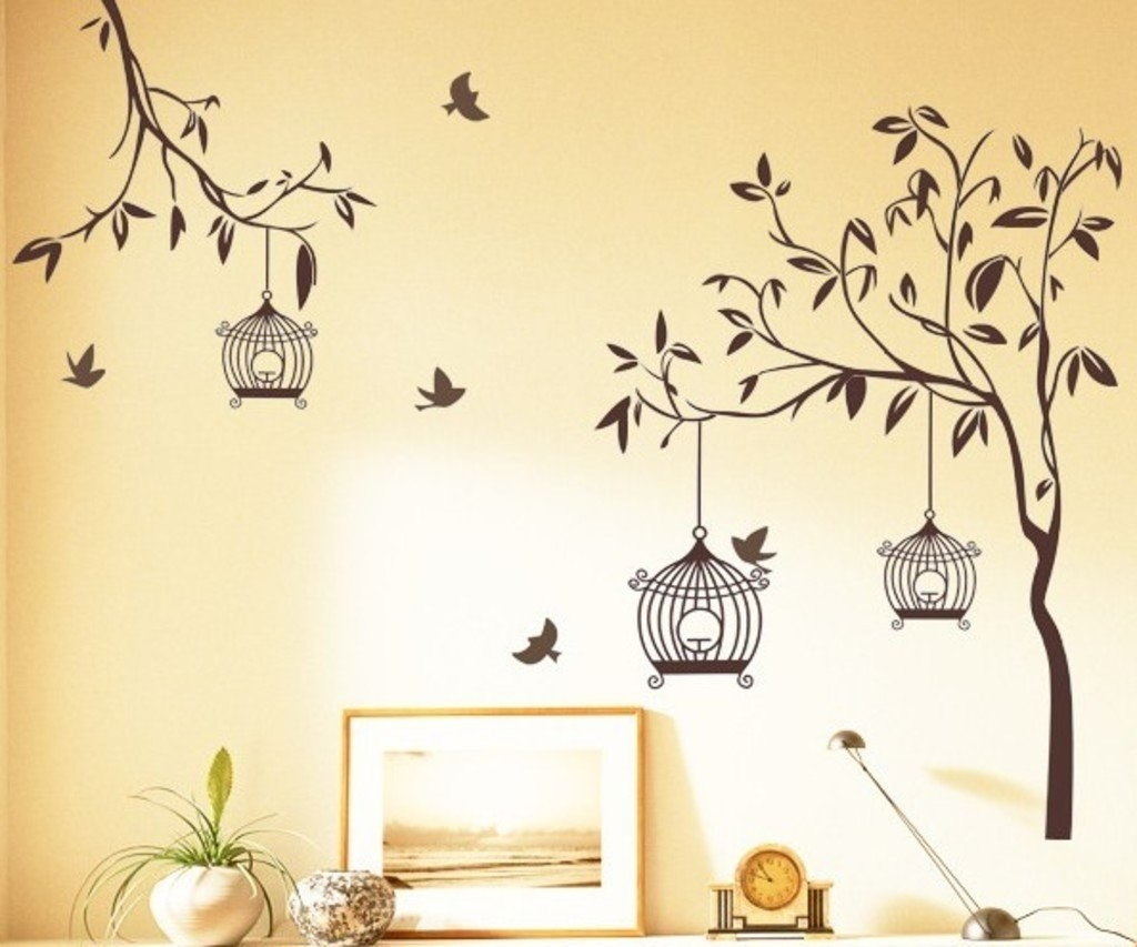 Wall decals stuck on a wall, depicting a trees, flying birds, and open bird cages.