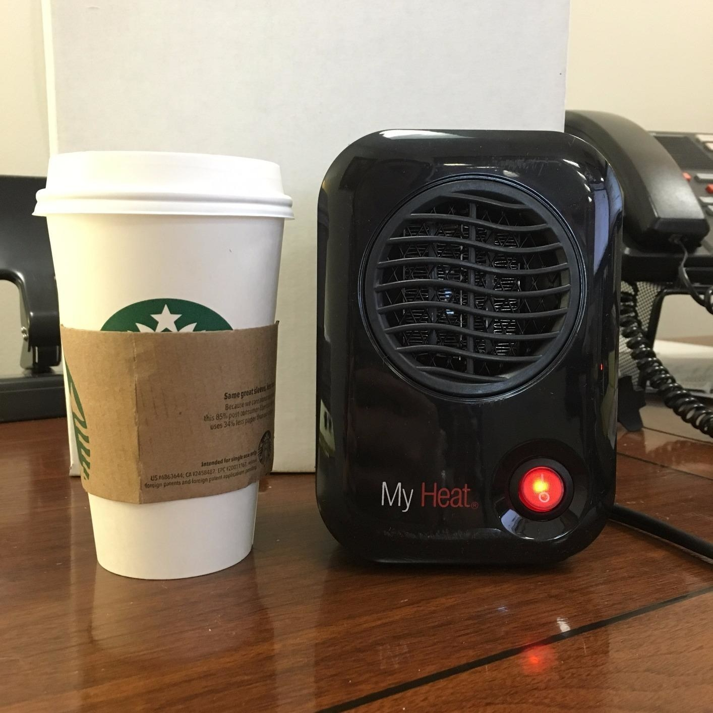 A reviewer showing their small black heater, about the same height as a starbucks coffee cup