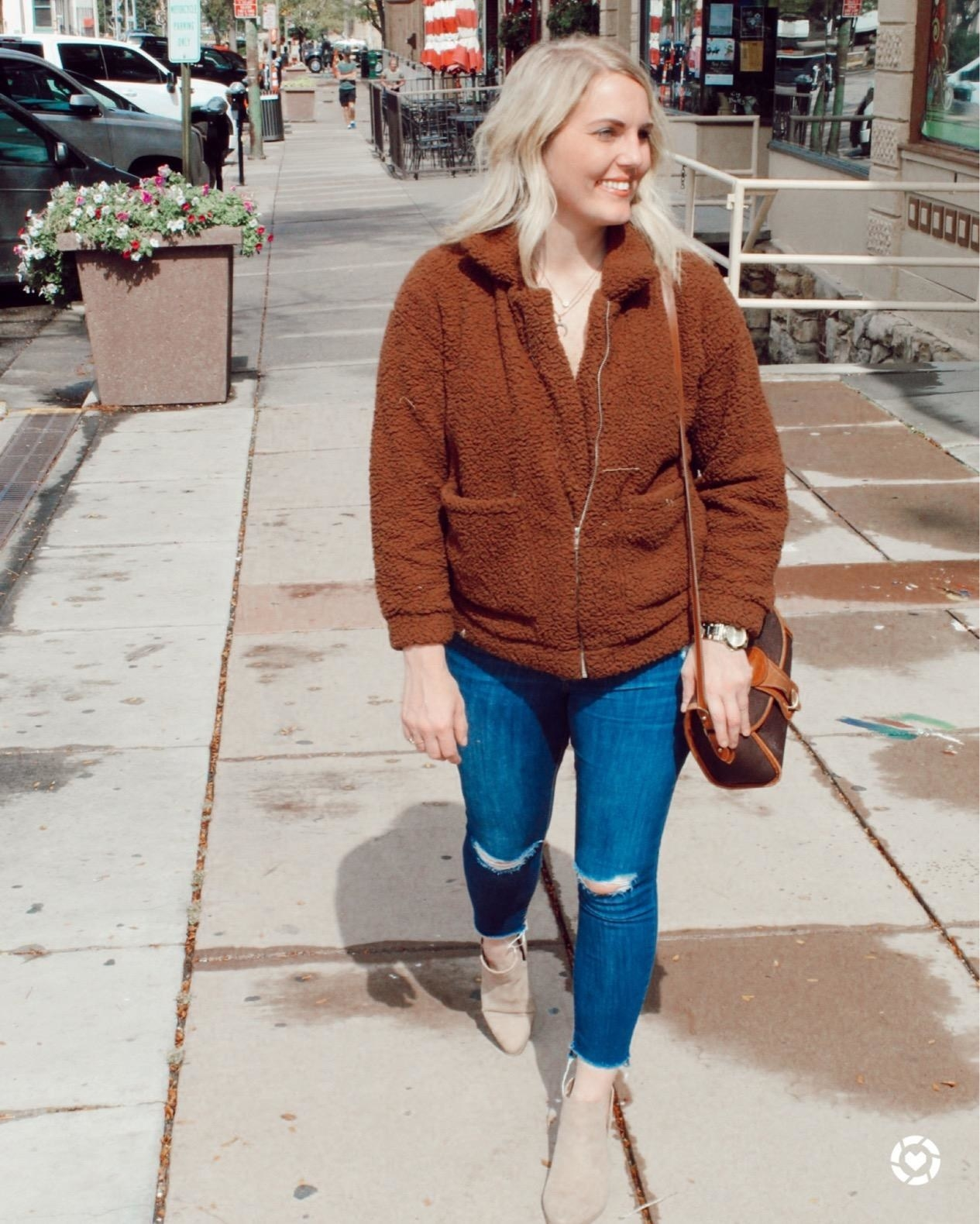 A reviewer in the tan teddy coat with zipper and pickets on the front