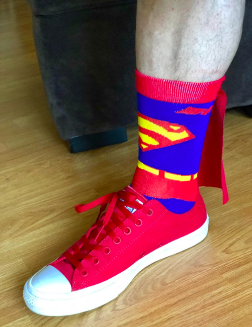 A reviewer wearing the superman logo crew socks with a cape off the back