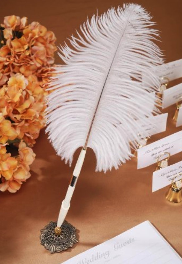 the feather pen standing up in a vintage-looking metal base