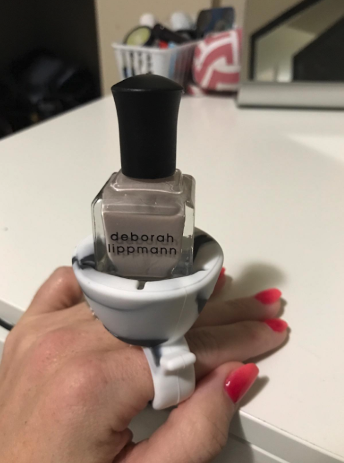 "Reviewers hand with a gray nail polish holder on one finger like a ring. The ""top"" of the ""ring"" has a silicone container you'd stick the bottle in so it'll hold in place."
