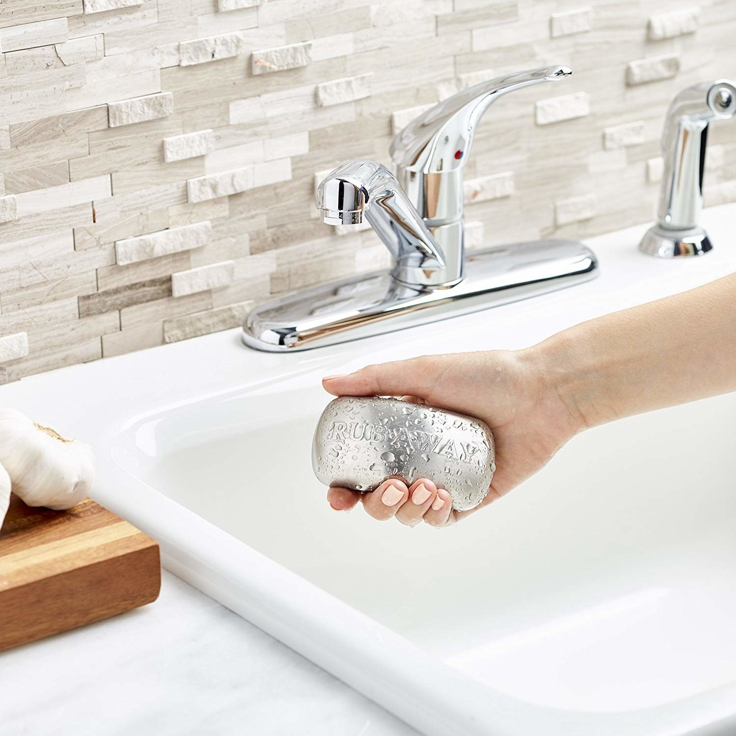 A person holding the kitchen bar over a sink