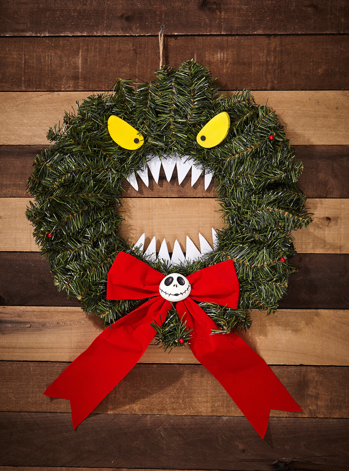 The wreath as a face with scary eyes on top and teeth in the center, with a red bow with Jack Skellington's face in the middle