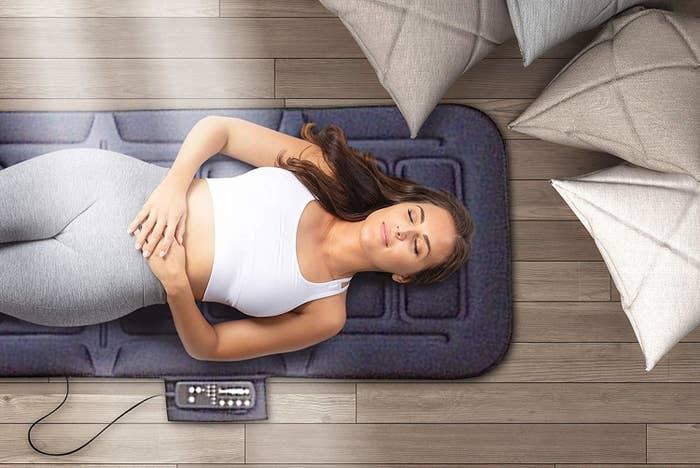 Person laying on padded massage mat that's slightly larger than a yoga mat. It has a connected remote.