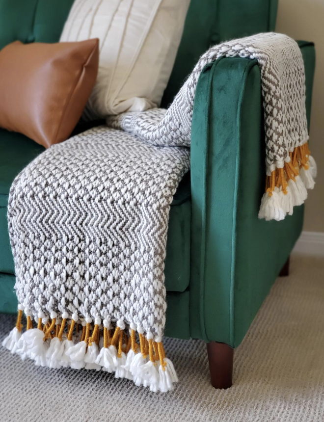 a customer's photo of the woven blanket in grey and white with mustard yellow accents