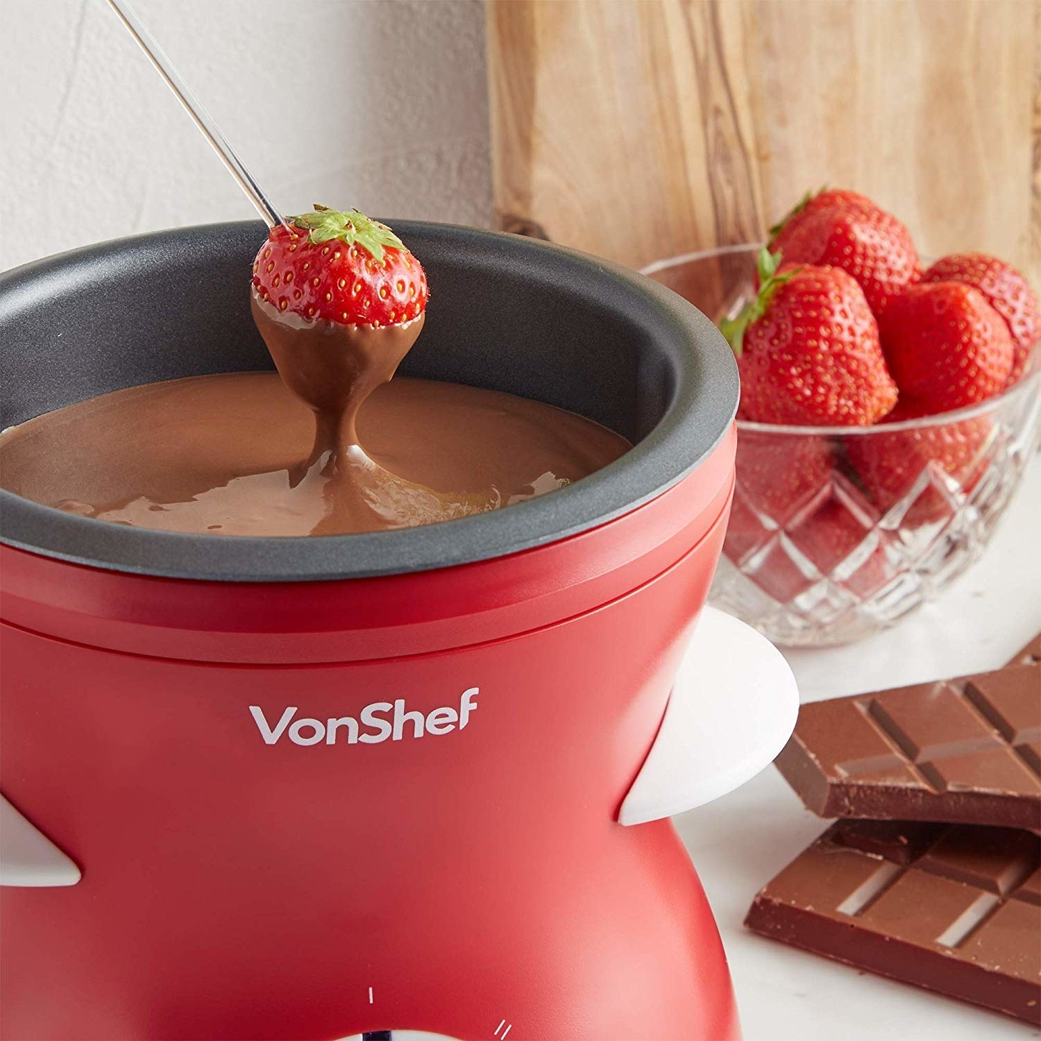 The red fondue maker filled with chocolate, with a strawberry being dipped in