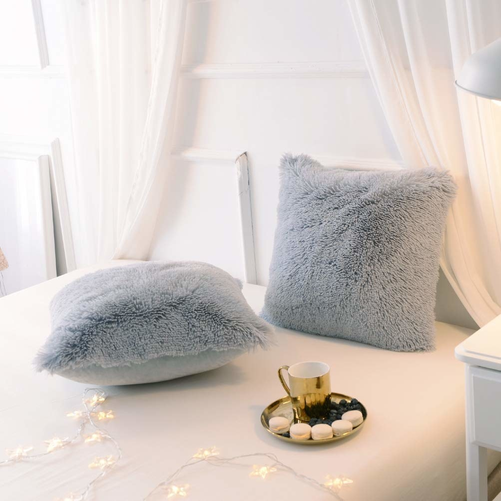 The grey pillows with fur on one side and velvet on the other
