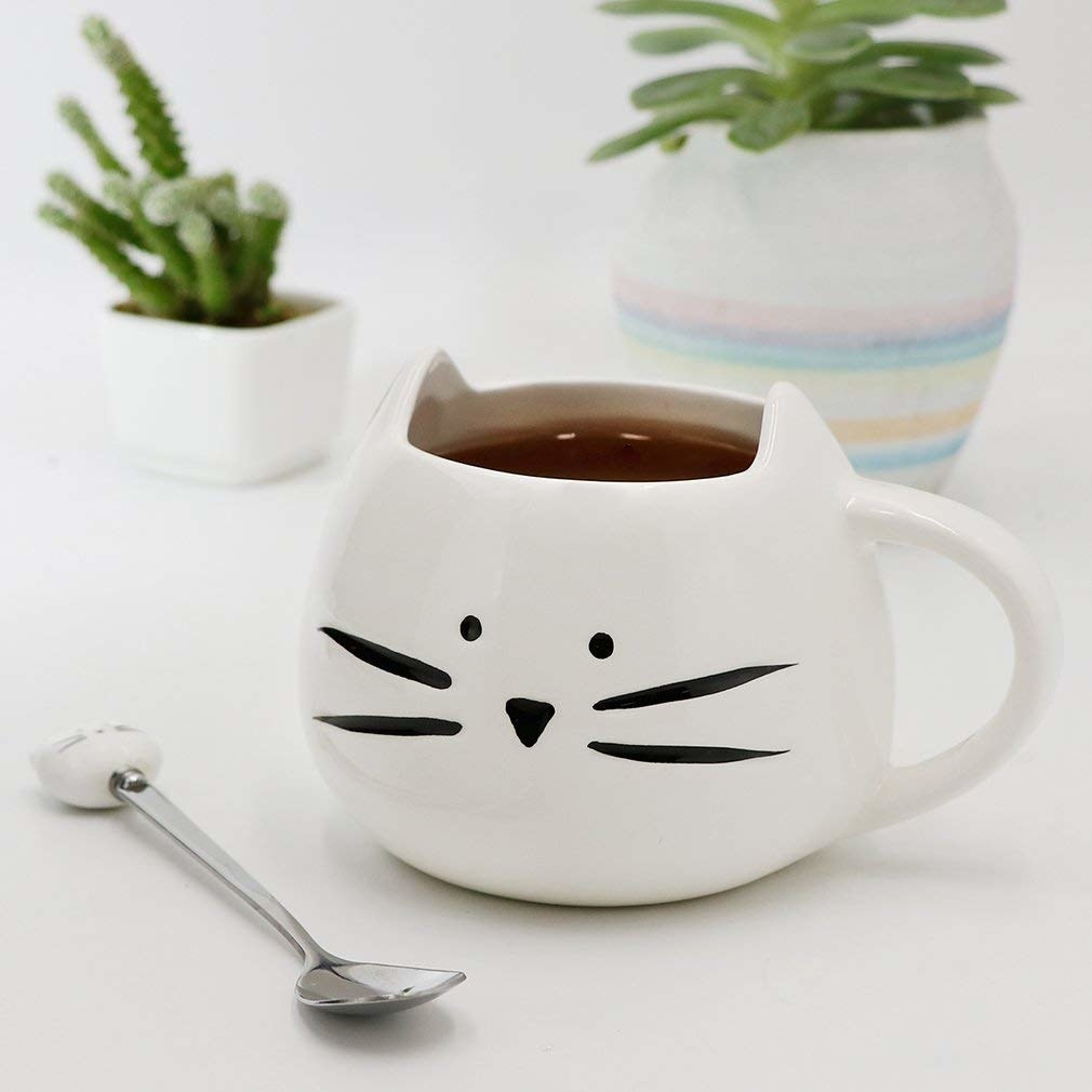 A small coffee mug with a cat face drawn on the front There is a small spoon with a cat face at the end of the handle