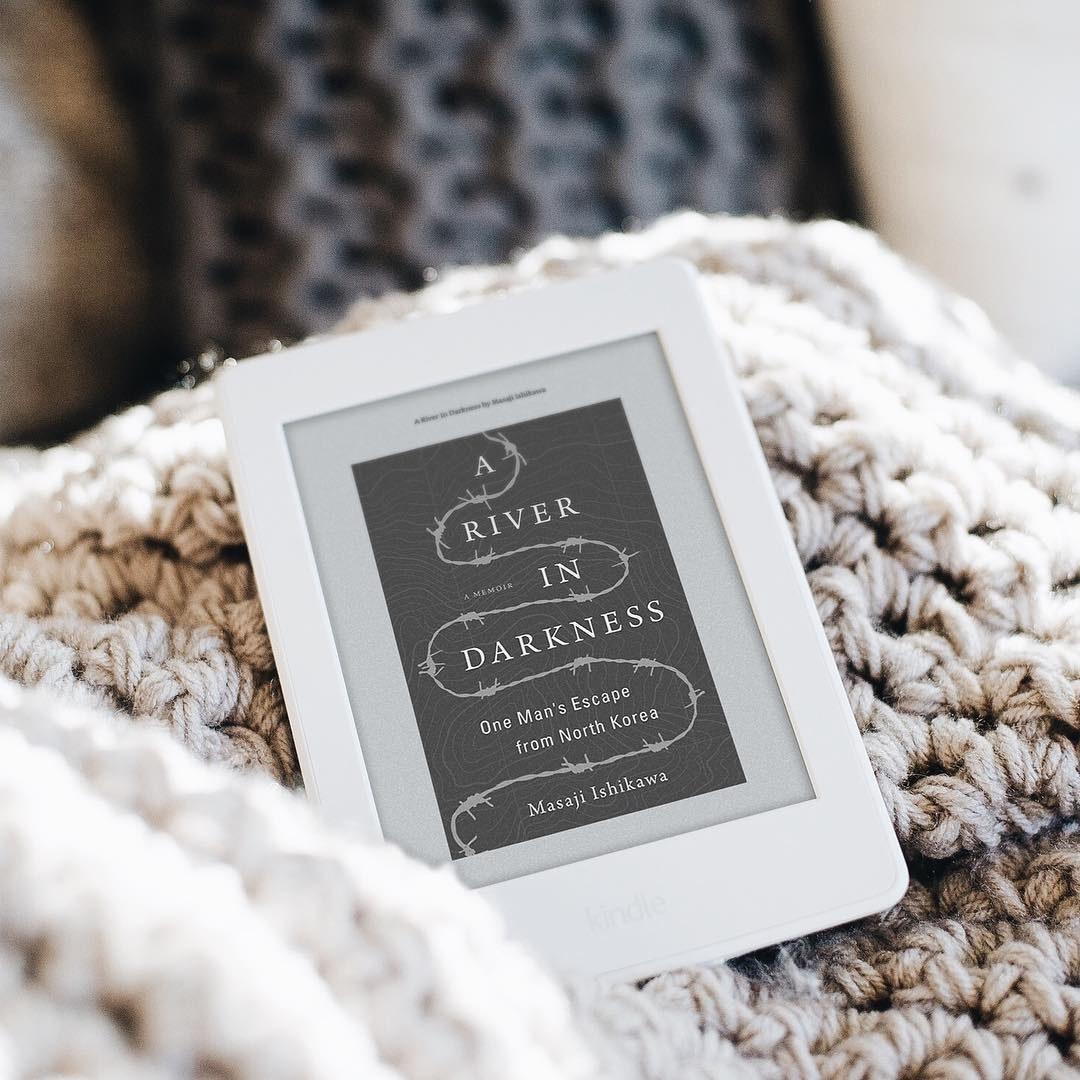 A Kindle eReader lying on a large knit blanket
