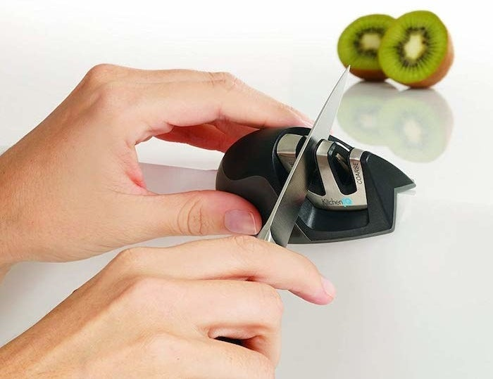 model's hand running a knife through one of the slots on the knife sharpener. It has two slots.