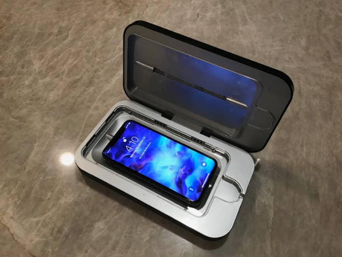 A black square case (the size of a large tablet but way thicker) is sitting on a surface. It has a lid which is open. The case has a phone (looks like a droid) sitting inside of it with a blue screen.