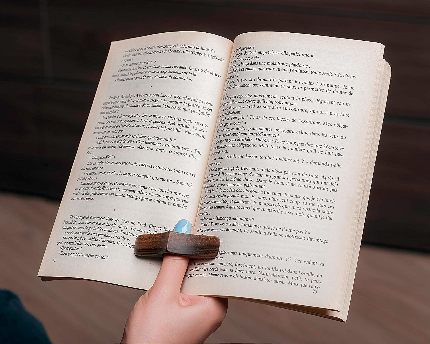 A person holding a paperback book open with a large wooden diamond-shaped ring on their thumb