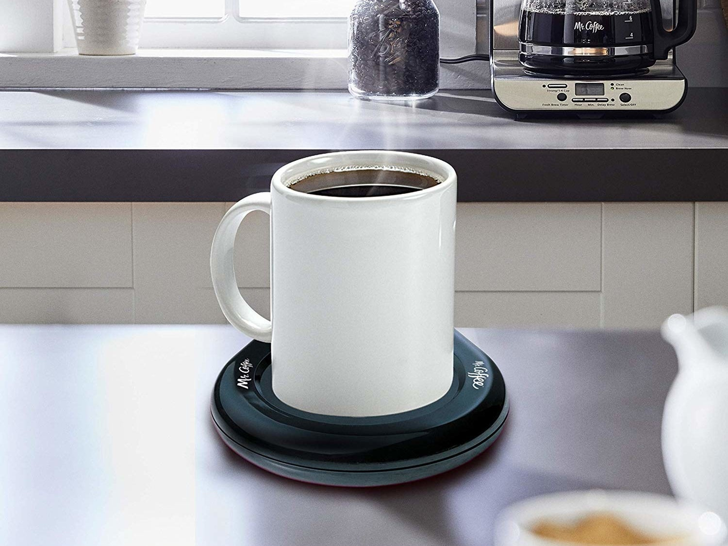 A mug filled with coffee placed on the warmer