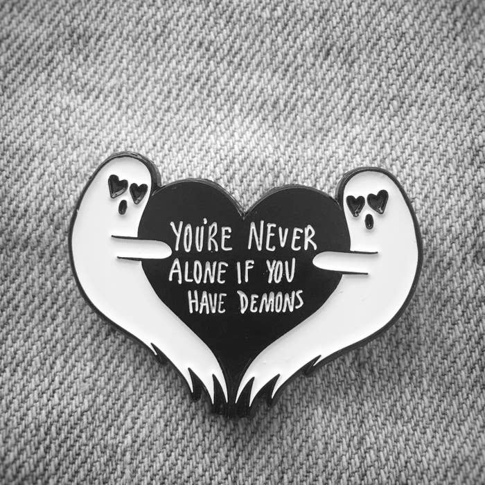 "the pin of two ghosts with heart eyes hugging either side of a black heart that says ""you're never alone if you have demons"""